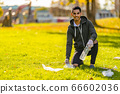 Smiling and committed volunteer cleaning garbage on grass at park 66602036