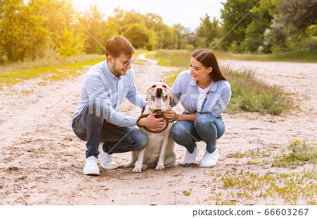 Portrait of happy young couple hugging their cute dog 66603267