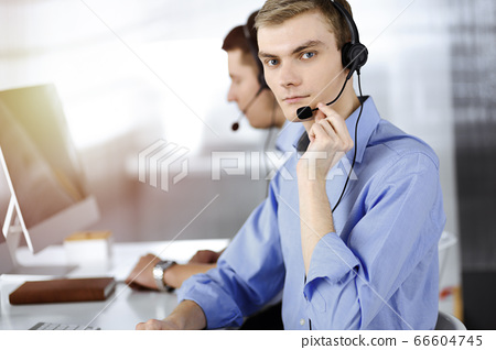 Two young men in headset, sitting at the desk in a sunny modern office, listening to the clients. Call center operators at work 66604745