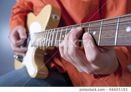 Fingers of a guitar player playing electric 66605193
