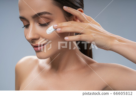 Smiling young woman using face cream on cheek 66605812