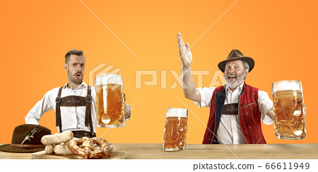 Smiling men with beer dressed in traditional Austrian or Bavarian costume holding mug of beer at pub or studio. The celebration, oktoberfest, festival 66611949