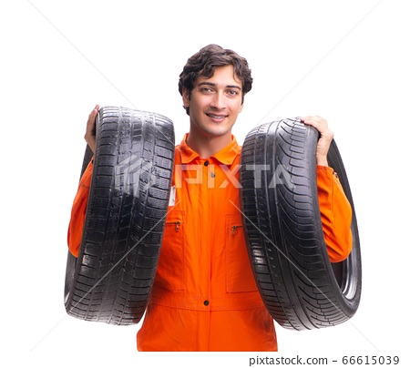 Young garage worker with tyre isolated on white 66615039