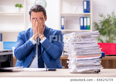Young male employee making copies at copying machine 66624259