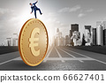 Businessman with giant golden euro coin 66627401