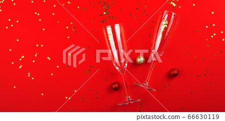 Champagne glasses with golden confetti on red 66630119