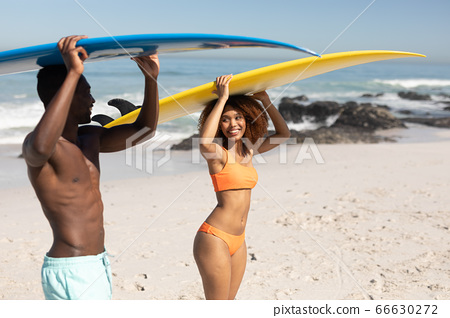 Mixed race couple holding surf boards on the beach 66630272
