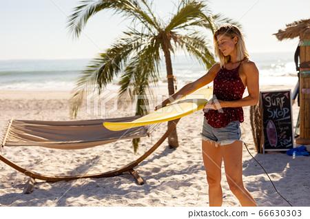 Caucasian woman holding surf board on beach 66630303