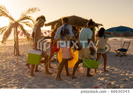Mixed race friends group walking on beach 66630343
