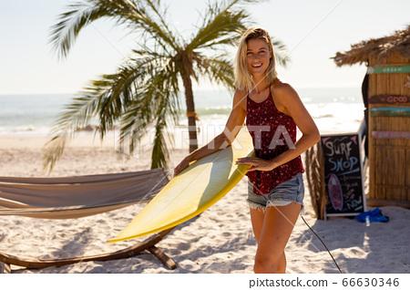 Caucasian woman holding surf board on beach 66630346