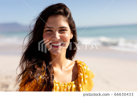 Caucasian woman standing on the beach 66630433