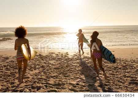 Young mixed race people holding surf boards on beach 66630434