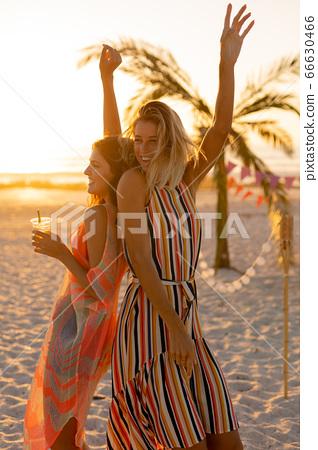 Mixed race friends having fun on beach 66630466
