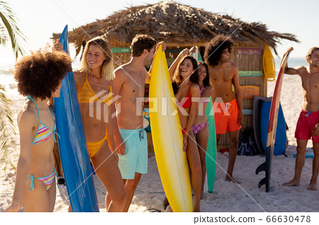 Young mixed race people holding surf boards on beach 66630478