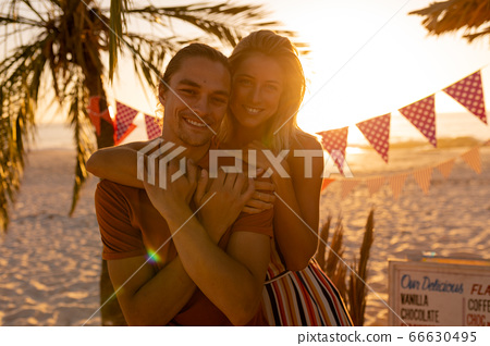 Caucasian friends hugging on beach 66630495