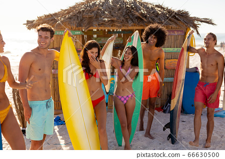 Young mixed race people holding surf boards on beach 66630500