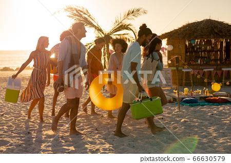 Mixed race friends group walking on beach 66630579