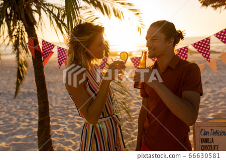Caucasian couple smiling and drinking alcohol on beach 66630581