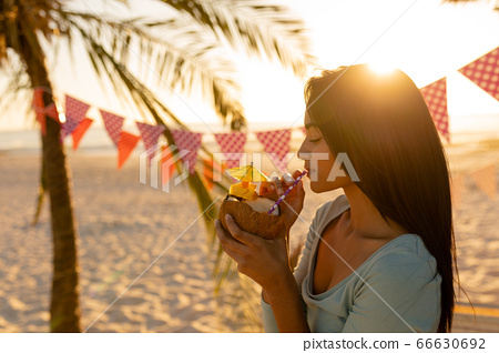 Young mixed race woman drinking cocktail on beach 66630692