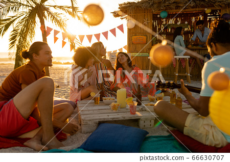 Mixed race friends group having fun on beach 66630707