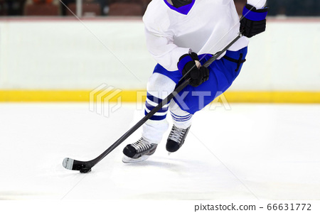 Ice hockey player dribbling puck on rink 66631772
