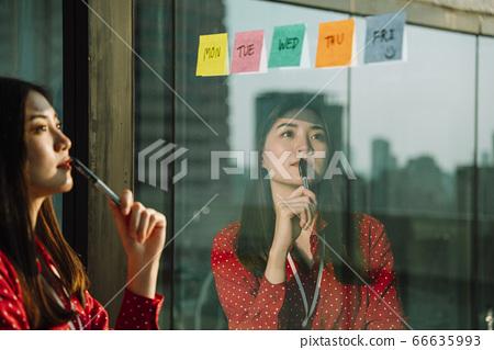 Beautiful young asian thai businesswoman in red shirt. Thoughtful 66635993