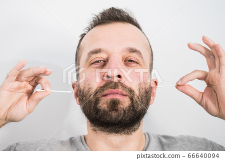 Man removing wax from ear using Q-tip 66640094