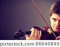 Man man dressed elegantly playing violin 66640849
