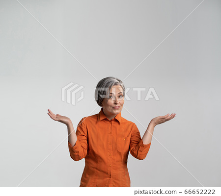 Surprised mid-aged woman presents an advertising product smiling at camera with opened palms. Copy spase for text. Square template for publication on social networks 66652222