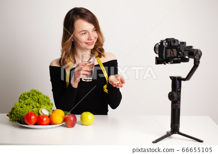 Woman holding an omega-3 fish oil vitamin tablet and a glass of drinking water in her room and recording a video blog on her phone. 66655105
