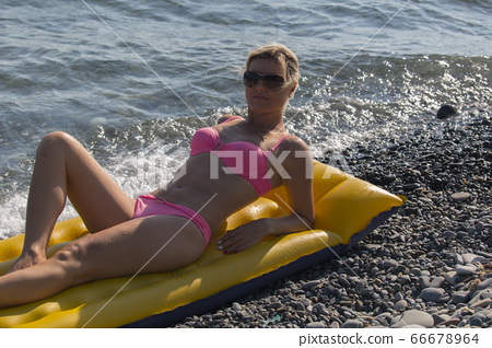 Happy woman smiling in sunglasses on an air mattress by the sea 66678964