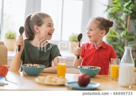 Happy children having breakfast 66690733