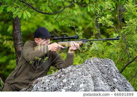 Male with a gun in hunting period 66691899