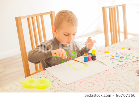 Little boy with brush and paint at home 66707360
