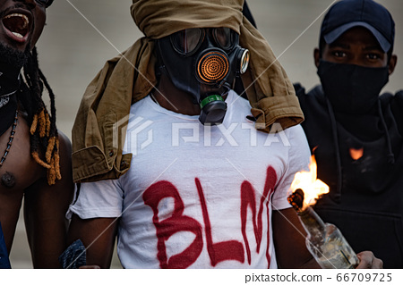 afroamerican men hold burning glass bottle in hands 66709725