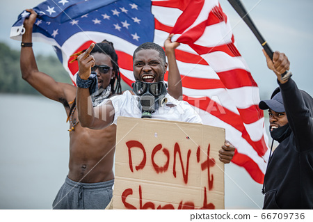 Black lives matter protests go global. three afroamerican people with posters in the street 66709736