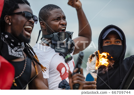 angry black people in gas mask riot, set fire to bottles 66709744