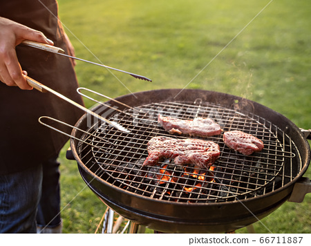 Scene of a man grilling meat outdoor. 66711887
