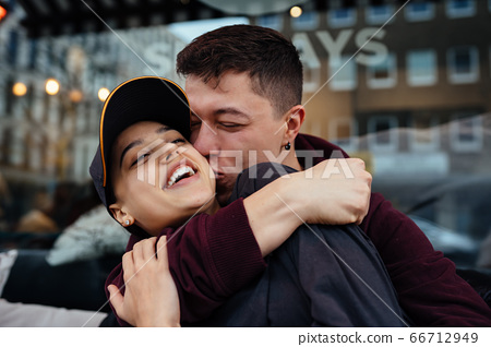 Guy and a girl are hugging at a table in a outdoor cafe. 66712949