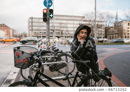 Young woman posing in a parking lot with bicycles 66713202