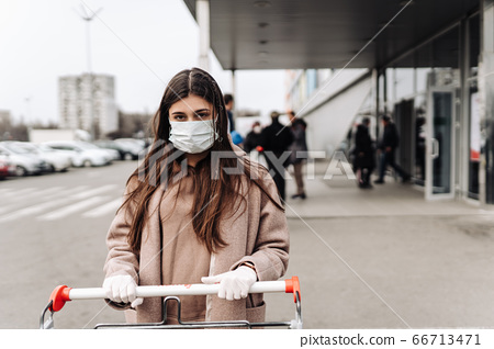 Young woman wearing protection face mask against coronavirus 2019-nCoV pushing a shopping cart. 66713471