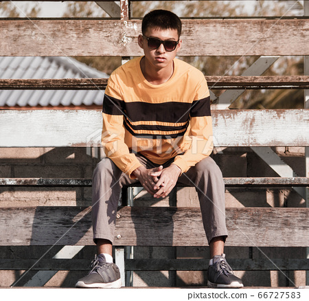 Portrait of a young handsome teenager boy in yellow long sleeve t-shirt and wear black glasses, sit on wooden stage outdoors. lifestyle people concept. 66727583