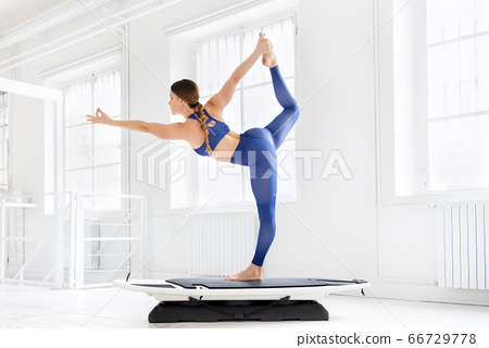 Woman doing a dancer pose during a yoga workout 66729778