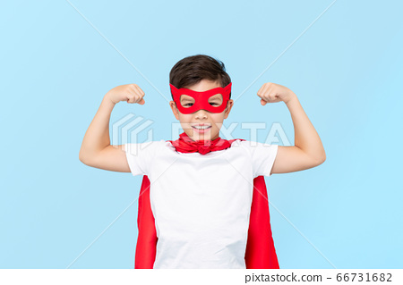Cute superhero boy in red mask and cape flexing arm muscles 66731682