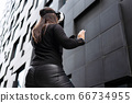 Back Of Woman Wearing Virtual Reality Technology Glasses Against Modern Building 66734955