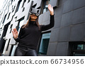 Woman Portrait Using Virtual Reality Glasses And Black Outfit In Futuristic City 66734956