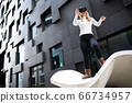 Blonde Woman Wearing Virtual Reality Glasses Against Futuristic Building 66734957