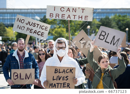 Black lives matters protesters holding signs and marching outdoors in streets. 66737123