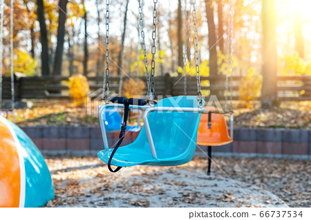Empty chair multicolored colorful chain swing carousel at old vintage retro entertainment amusement park autumn sunset evening outdoor. Past childhood memories concept. Quarantine closed public area 66737534