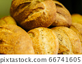 Fresh baked loaves of bread lying on the shelf in grocery store. Flavorful bakery in supermarket. Retail shop, food. 66741605